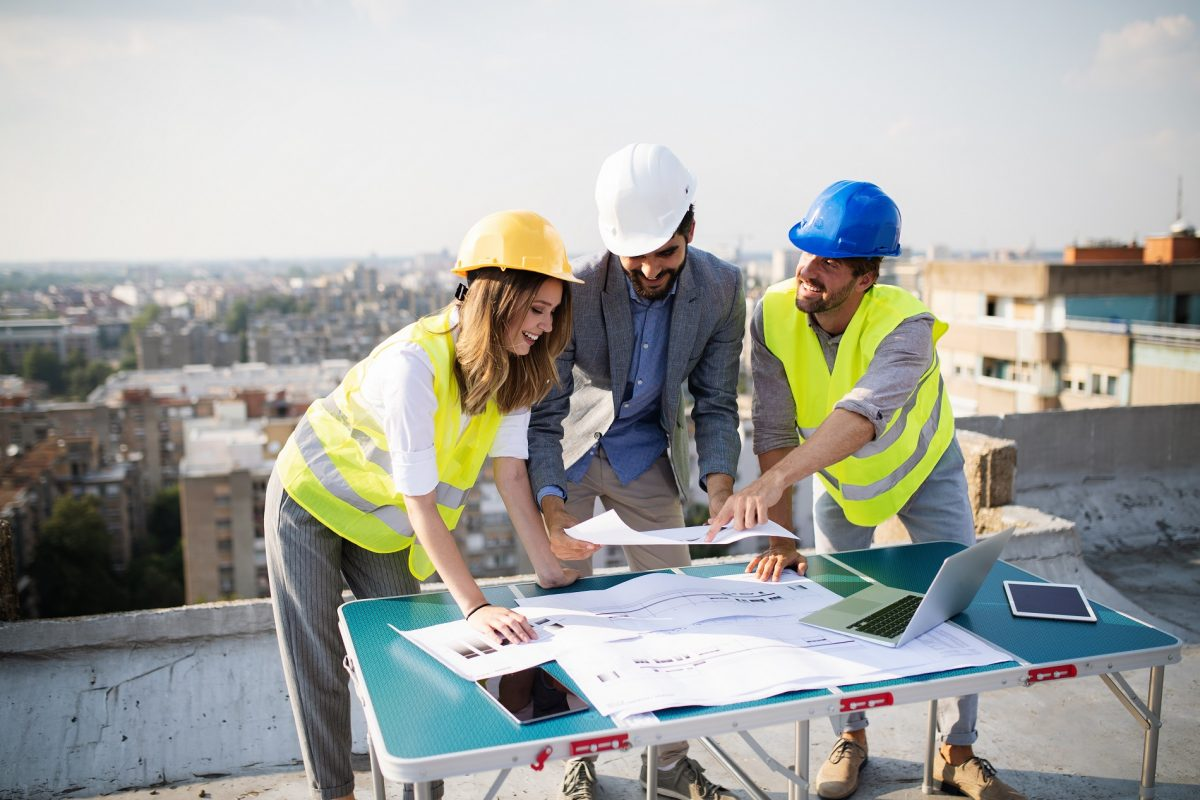 Team of architects and engineers people in group on construciton site check documents